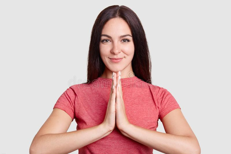Le portrait horizontal de la jeune femme fidèle de brune maintient des plams dans le geste de prière, habillé en passant, des pos photos libres de droits