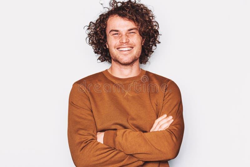 Le portrait horizontal de studio du sourire masculin beau heureux largement, posant pour la publicité utilise le pull brun images stock