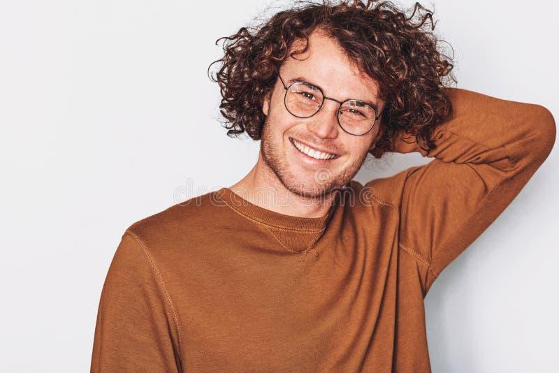 Le portrait horizontal de vue de face du jeune mâle de sourire beau avec les cheveux bouclés, porte les lunettes à la mode ronds image libre de droits