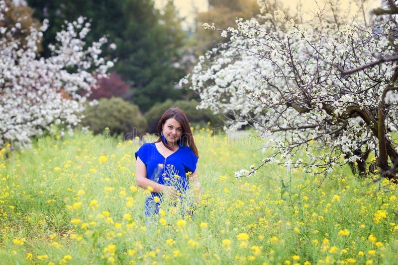 Le portrait horizontal des pruniers de floraison proches de jeune femme caucasienne de brune dans la moutarde jaune mettent en pl photo stock