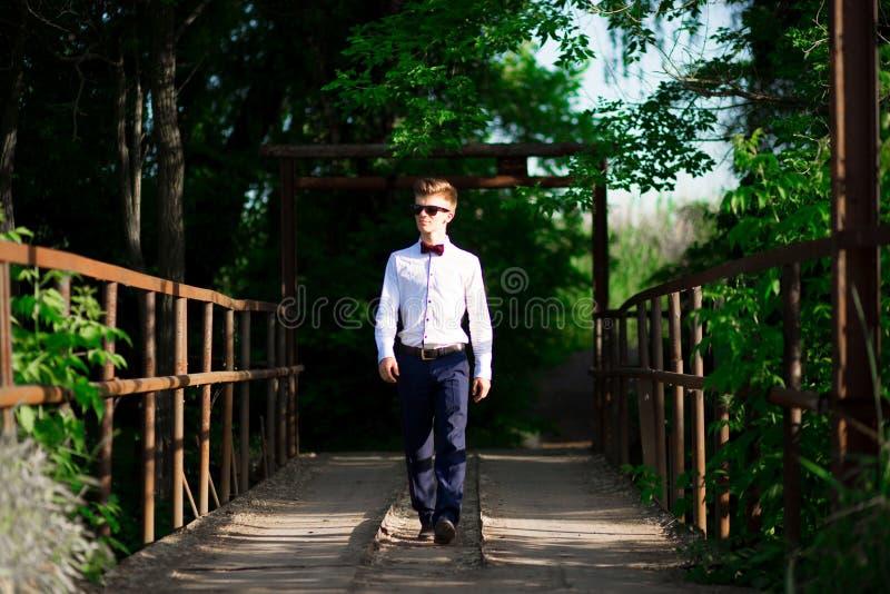 Le portrait intégral d'un jeune homme d'affaires habillé dans un costume élégant et des lunettes de soleil entre avec confiance d photo libre de droits