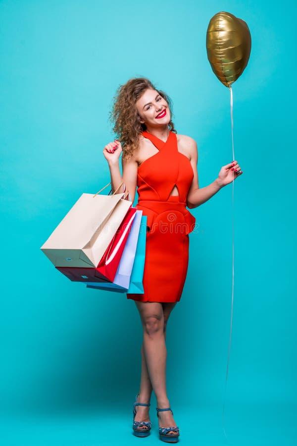 Le portrait intégral d'une femme enthousiaste heureuse dans la robe rouge tenant et tenant les paniers colorés et le ballon d'or  photographie stock libre de droits