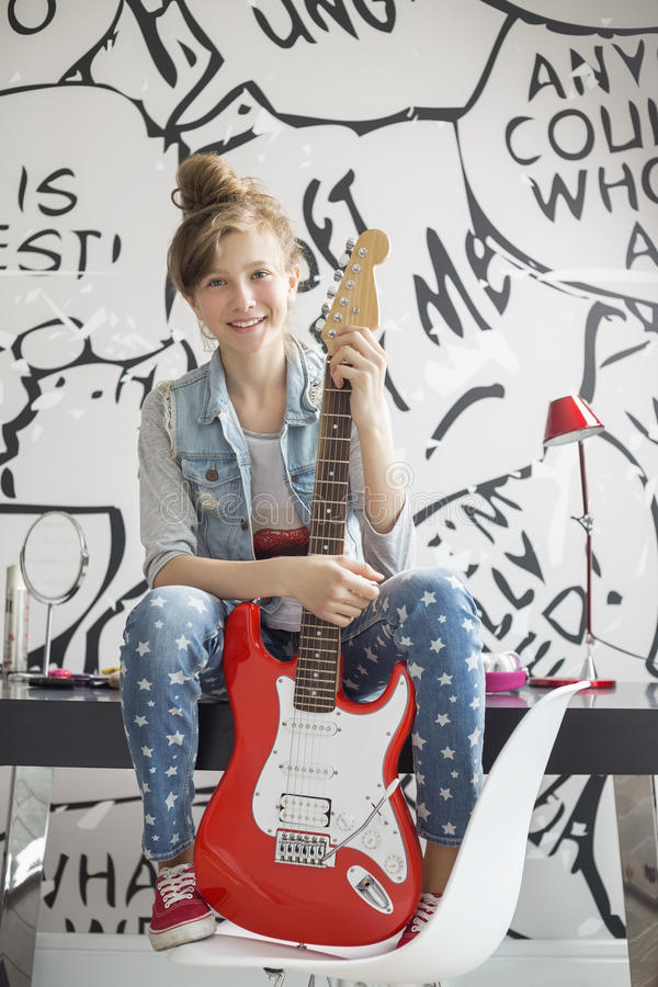 Le portrait intégral de la fille avec la guitare électrique se reposant sur l'étude ajournent à la maison photo stock