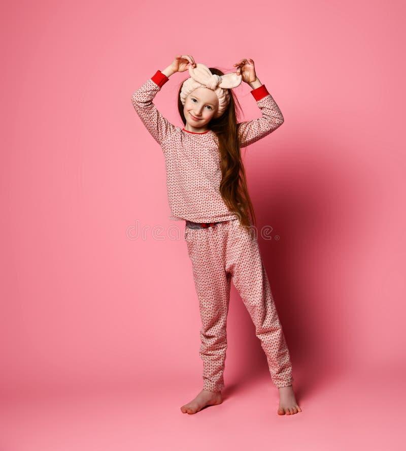 Le portrait intégral de la fille séduisante dans ses pyjamas roses et un bandeau mou est peint dans le cadre images stock