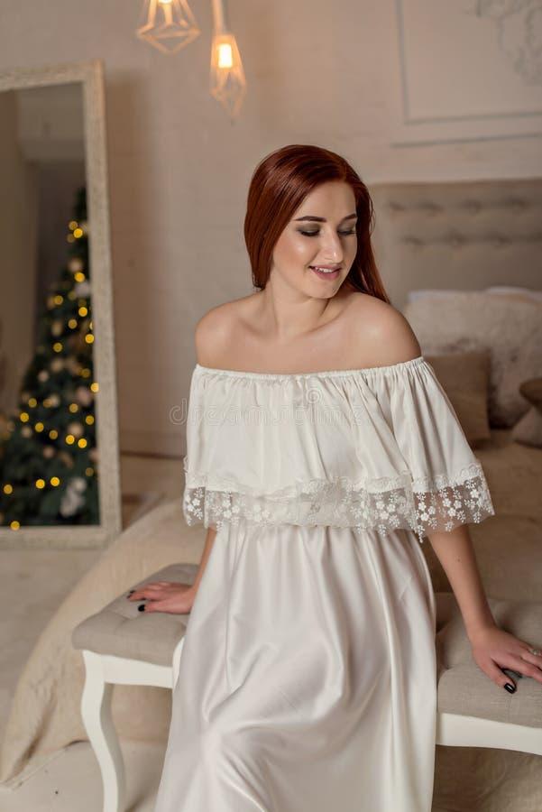 Le portrait intérieur de mode du beau maquillage de jeune femme et de soirée, porte égaliser la robe blanche Fille de modèle de s photographie stock libre de droits