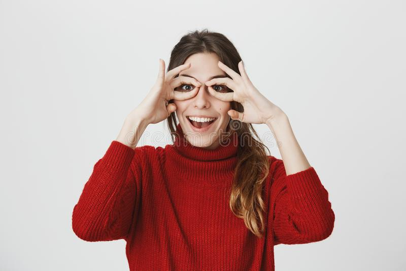 Le portrait jeune de l'étudiant drôle et créatif tenant ses mains s'approchent des yeux, montrant que les verres font des gestes  photo stock