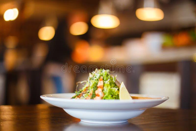 Le portrait latéral de la salade sous forme de piramide a compris la truite grillée, laitue, citron et l'a décoré photographie stock libre de droits