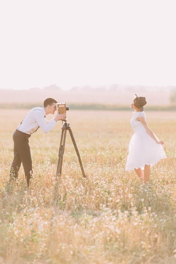 Le portrait latéral du vintage a habillé des nouveaux mariés dans le domaine Le marié prend des photos tandis que la jeune mariée images libres de droits