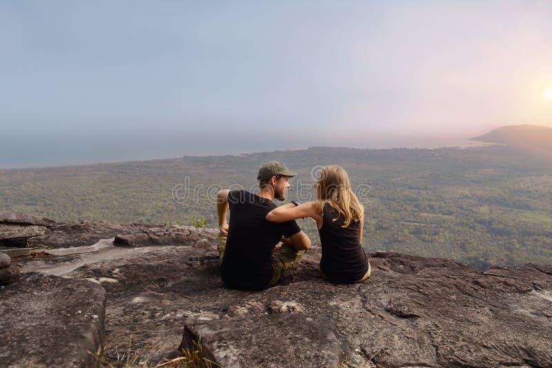 Le portrait lovly des couples dans l'étreinte se reposent sur un dessus de colline dans le coucher du soleil image stock