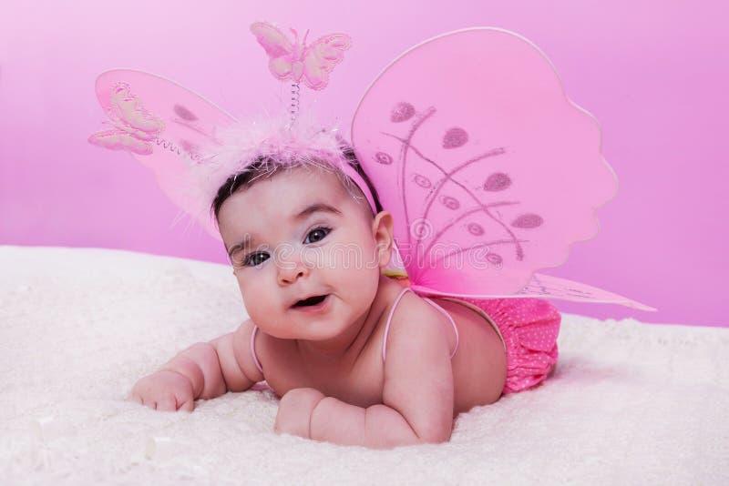 Le portrait mignon, joli, heureux, potelé et souriant de bébé, avec le papillon rose s'envole photographie stock libre de droits