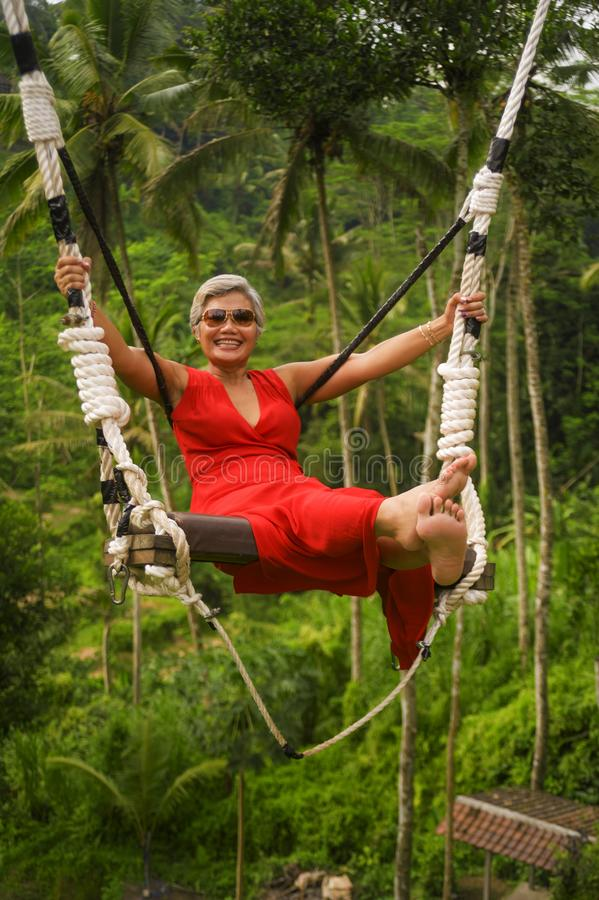 Le portrait naturel de mode de vie du milieu heureux attrayant a vieilli 40s - la femme 50s asiatique avec les cheveux gris et l' images libres de droits