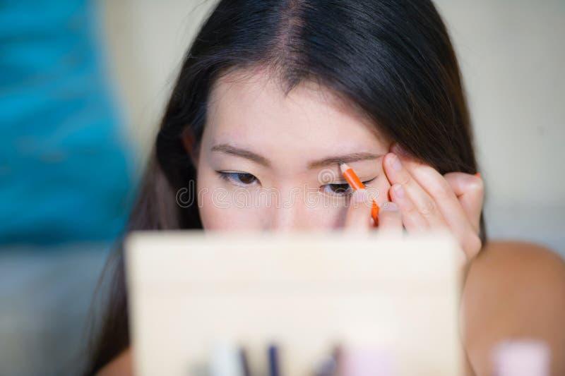 Le portrait naturel de mode de vie de la jeune belle et heureuse femme coréenne asiatique à la maison s'appliquant composent prof image stock