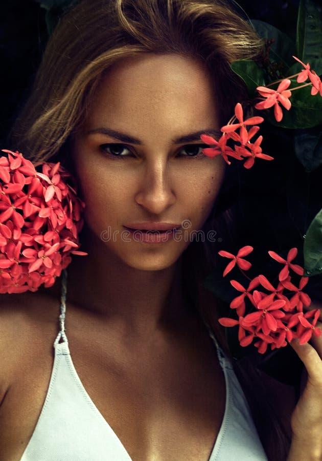 Le portrait naturel du beau modèle blond sexy de jeune femme avec la peau propre parfaite près de l'été fleurit en île tropicale photographie stock libre de droits