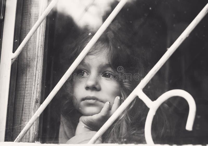 Le portrait noir et blanc de la petite fille triste regarde par la fenêtre image stock