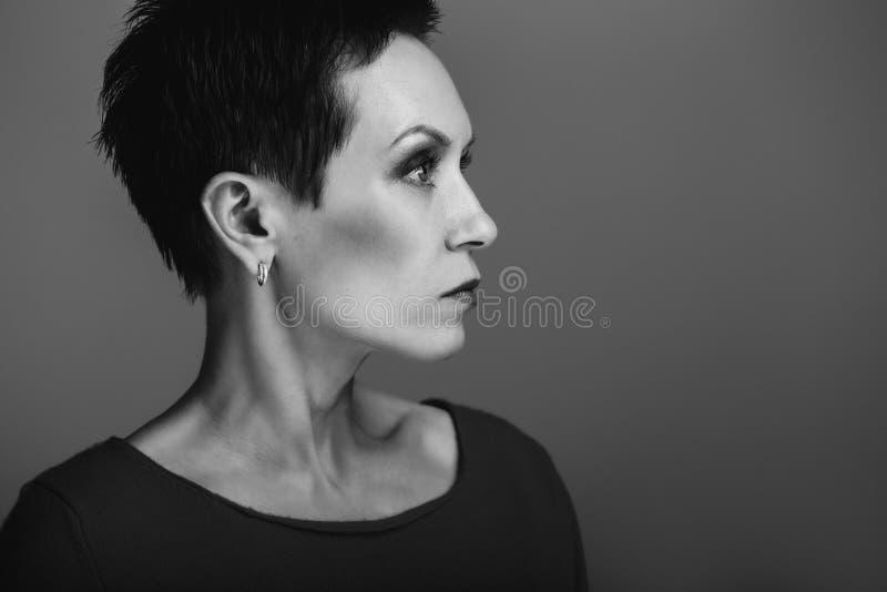 Le portrait noir et blanc de studio du beau milieu énervé frais a vieilli la femme caucasienne blanche de brune images stock