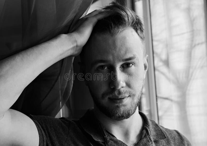 Le portrait noir et blanc du jeune homme de sourire corrige des cheveux photographie stock
