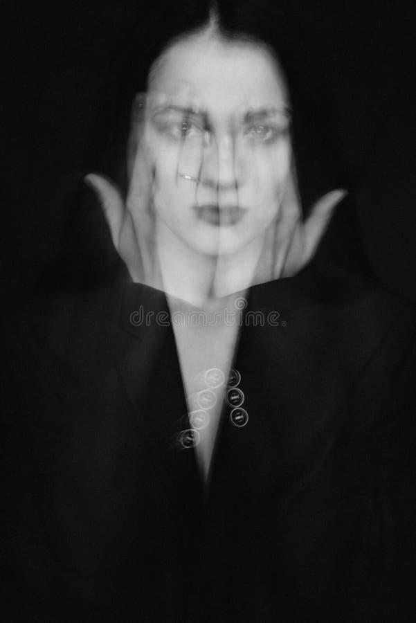 Le portrait psych?d?lique d'une fille avec des mains a ferm? le visage photographie stock