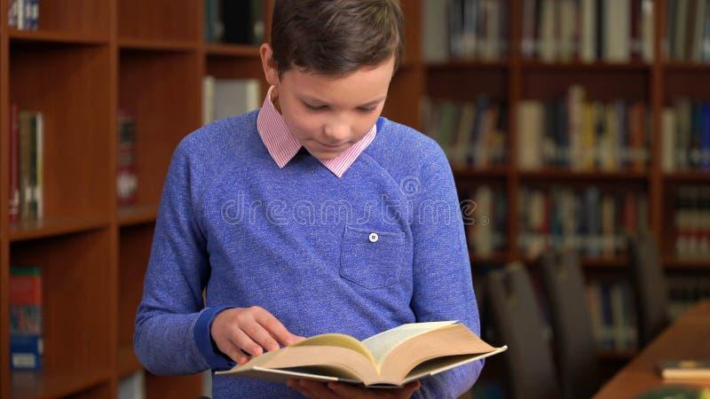 Le portrait a tiré de l'écolier et de la position mignons près de l'étagère dans la bibliothèque et la lecture un livre photos stock