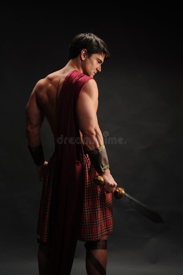 Le pose sexy dell'uomo per una fotografia fotografia stock