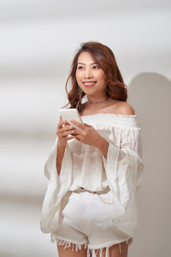Le positiv asiatisk kvinna med den h?rliga emotionella framsidan som lyssnar till musik ?ver vit royaltyfri foto