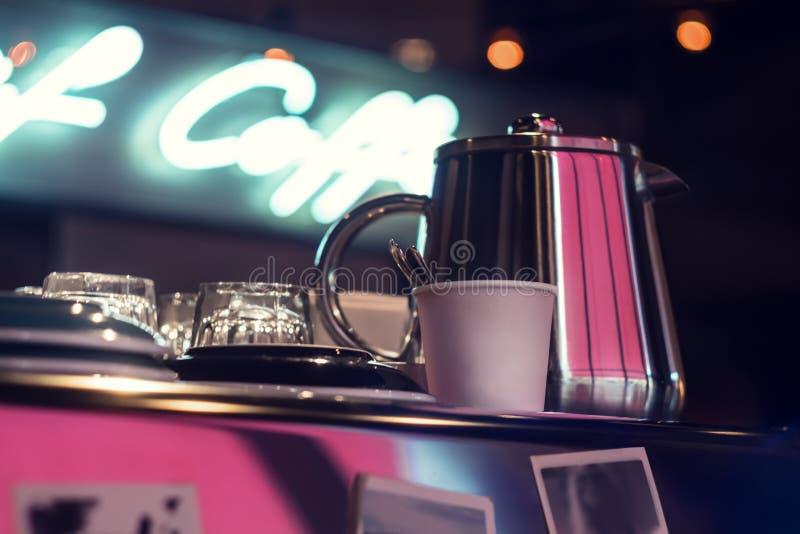 Le pot de café ou de thé, les tasses, les plats et les verres en verre se tiennent sur la machine d'expresso, derrière l'inscript images stock