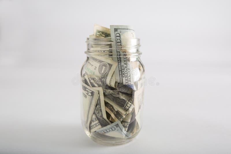 Le pot de maçon avec l'argent et le dollar différent s'élève photographie stock