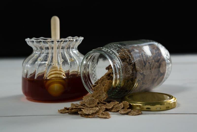 Le pot de miel et de blé s'écaille se renversant hors de la bouteille images stock