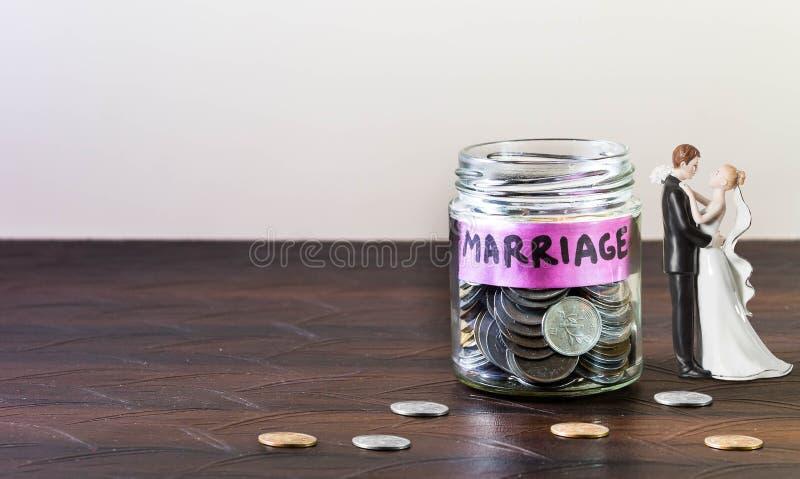 Le pot en verre complètement des pièces de monnaie et du mariage est marqué photo libre de droits