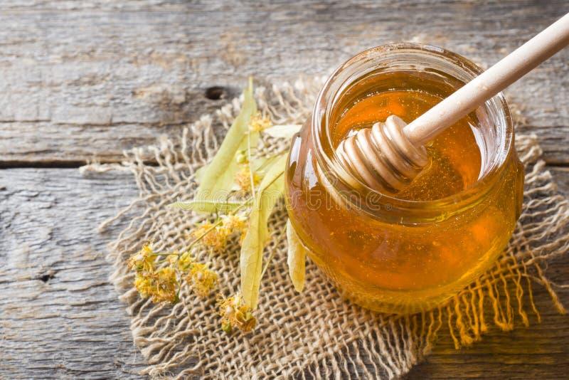 Le pot en verre de miel, tilleul fleurit sur le fond en bois image stock