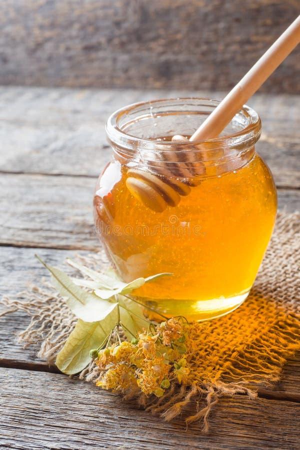 Le pot en verre de miel, tilleul fleurit sur le fond en bois photographie stock
