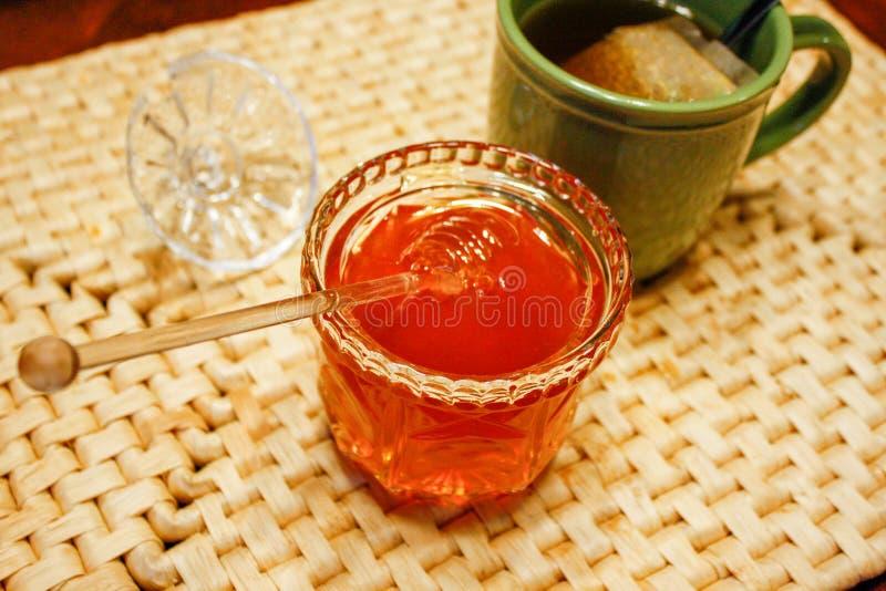 Le pot en verre ouvert avec du miel et le plongeur d'or a plongé à l'intérieur sur le tapis d'endroit photos libres de droits