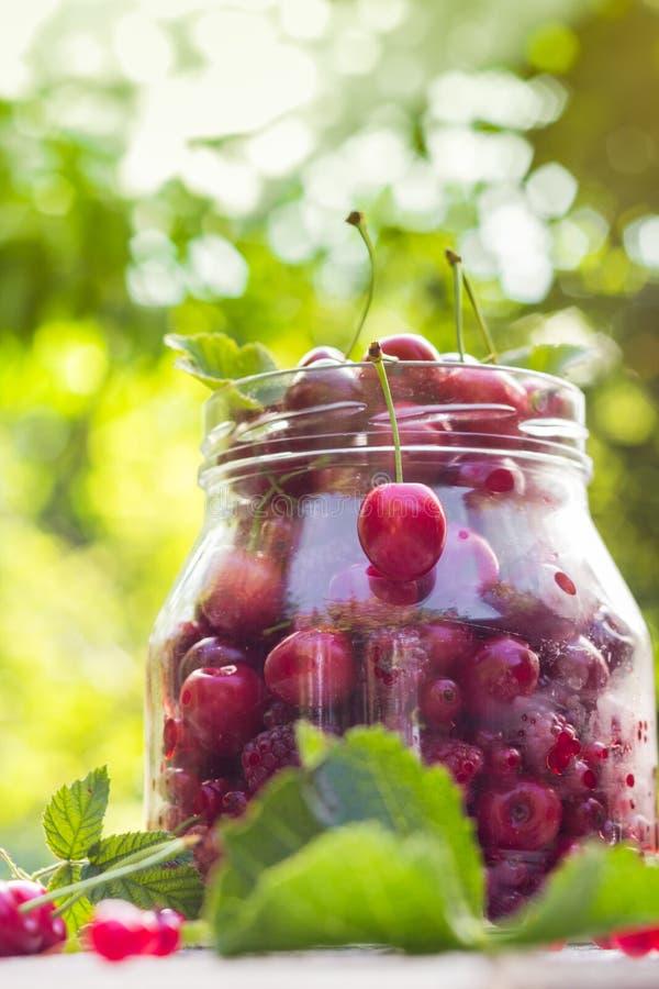 Download Le Pot En Verre Porte Des Fruits Des Cerises Et Des Framboises Photo stock - Image du coloré, nutrition: 76090694