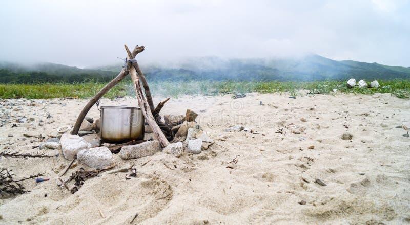 Le pot sur le feu sur un sable image stock