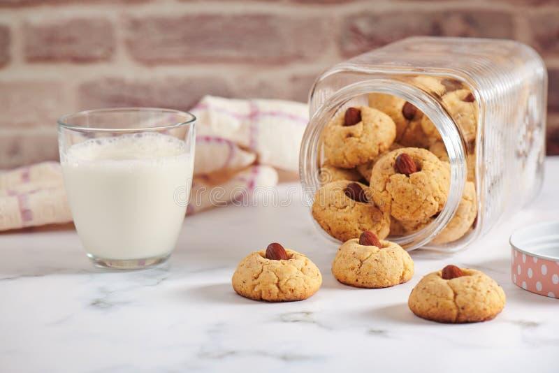Le pot tourné avec a lâché les biscuits d'amande, verre de lait image stock