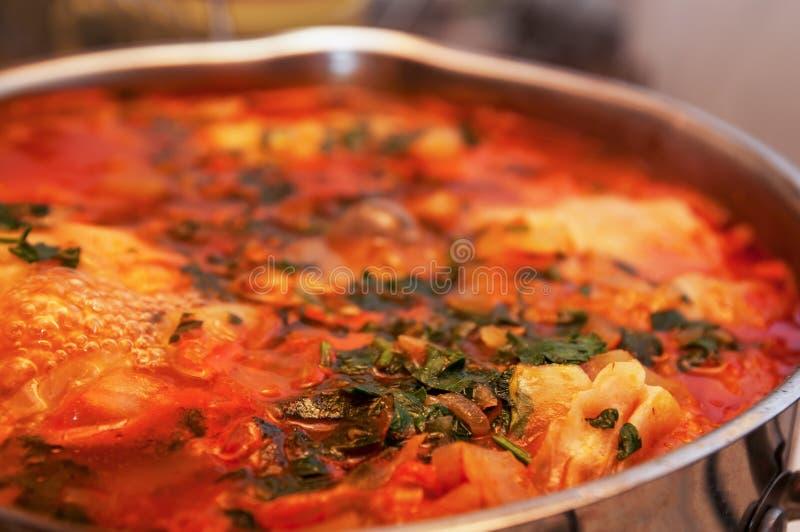 Le potage aux légumes rouge avec des verts se ferment dans la casserole photographie stock