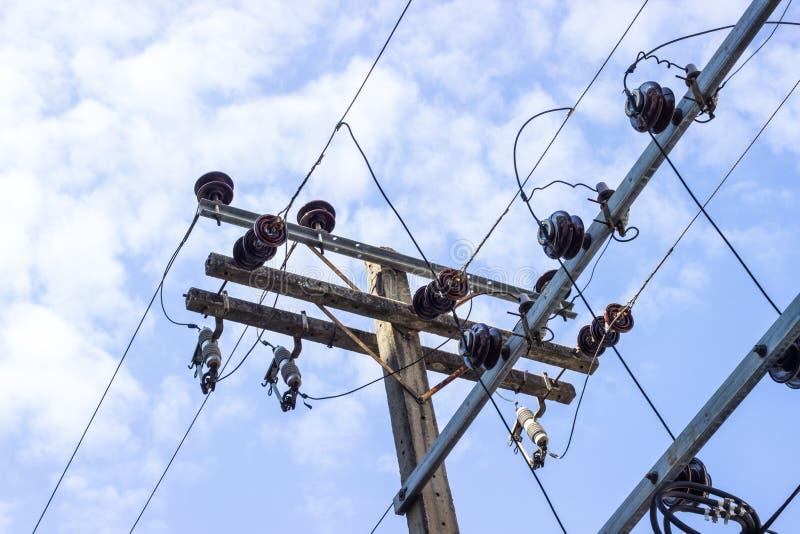 Le poteau électrique se relient aux fils électriques à haute tension sur l'agai image stock