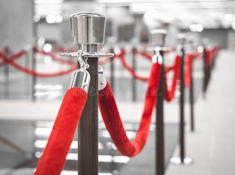 Le poteau de barrière de tapis rouge avec les cordes rouges a brouillé le fond intérieur image stock