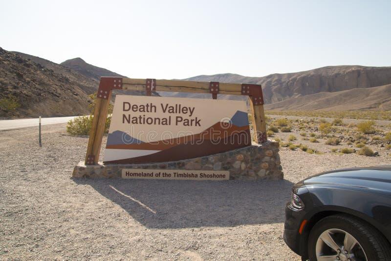Le poteau indicateur d'entrée de parc national de Death Valley, voiture rapide américaine de sport a garé dans l'avant, voyage pa photo libre de droits