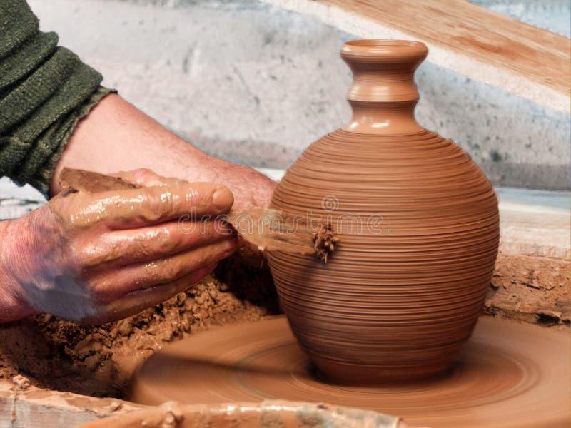 Le potier fait un vase à argile sur une roue de poterie images libres de droits