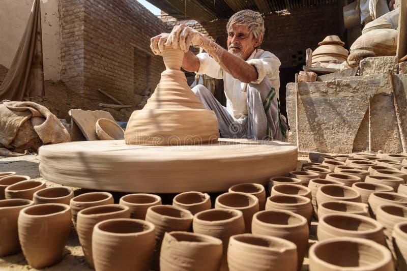 Le potier indien faisant des pots d'argile sur la poterie roulent dans Bikaner Rajasthan l'Inde photo libre de droits