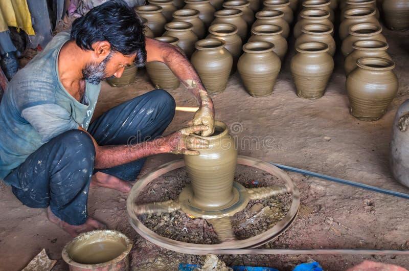 Le potier non identifié faisant l'argile arroser des pots sur la poterie roulent photo libre de droits