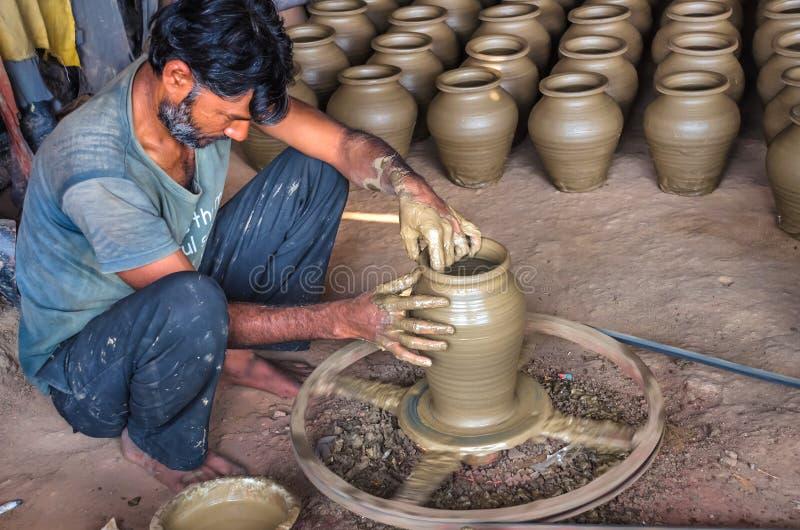 Le potier non identifié faisant l'argile arroser des pots sur la poterie roulent photographie stock libre de droits