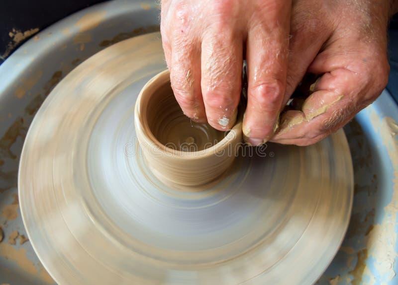Le potier sculpte de l'argile sur une roue de potier photos libres de droits