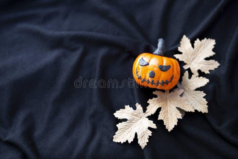Le potiron drôle de Halloween de conception avec le papier part sur le fond noir de texture de tissu photo libre de droits