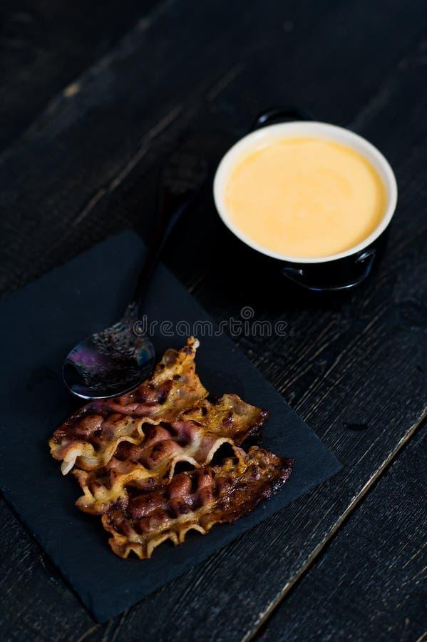 Le potiron mettent en purée la soupe avec le lard frit sur le fond noir images stock