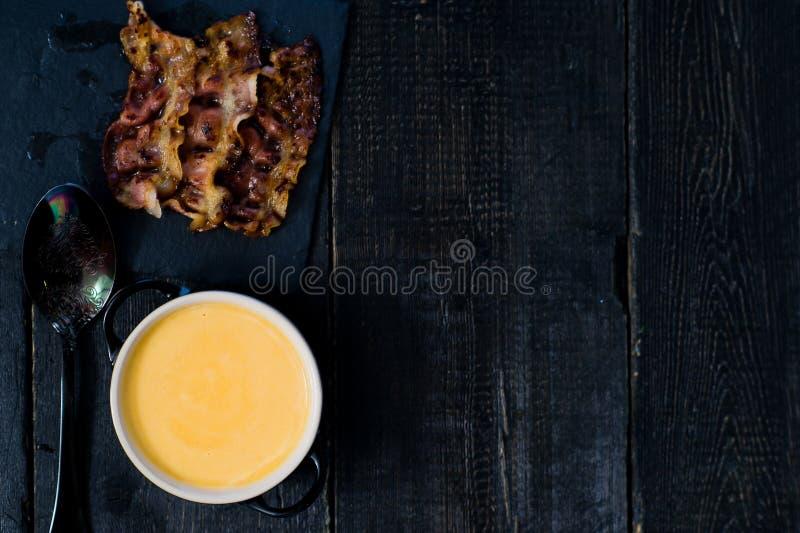 Le potiron mettent en pur?e la soupe avec le lard frit sur le fond noir photographie stock libre de droits