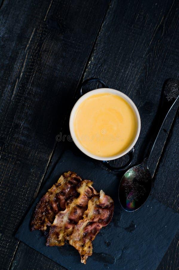Le potiron mettent en pur?e la soupe avec le lard frit sur le fond noir image libre de droits