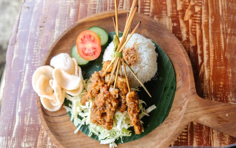 Le poulet assouvissent le riz et x28 ; Sate& x29 de Nasi ; oeufs servis, biscuits de crevette rose et poulet satay et sauce à ara image libre de droits