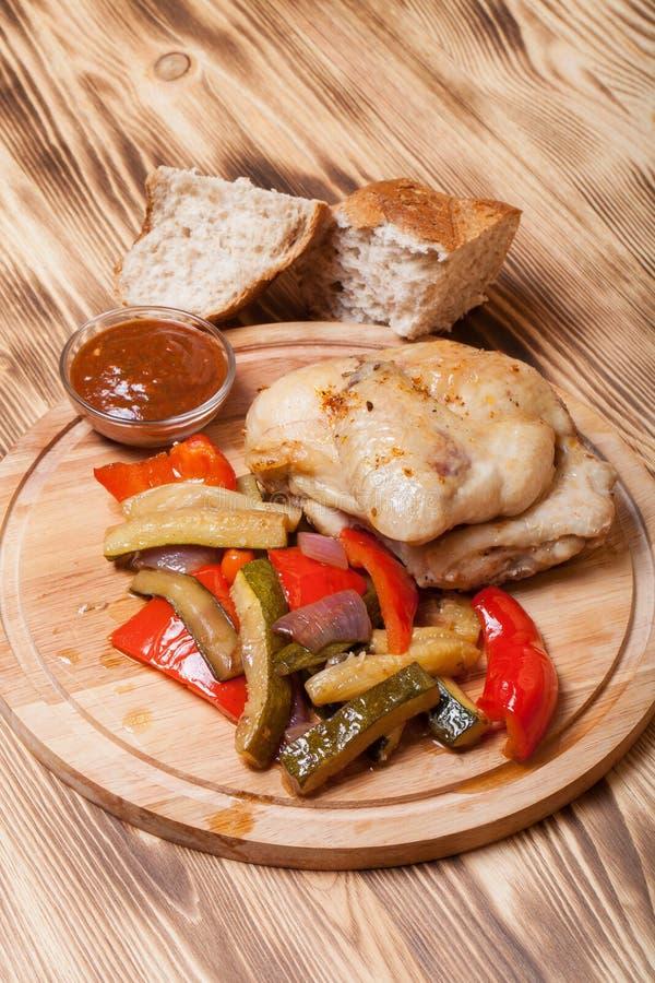 Le poulet avec des légumes a servi sur la planche à découper ronde sur brûlé photo libre de droits