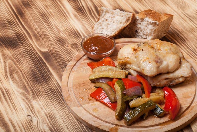 Le poulet avec des légumes a servi sur la planche à découper ronde sur brûlé photographie stock libre de droits